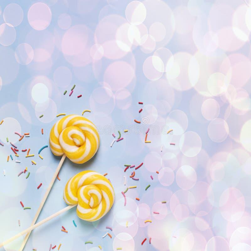 Concepto de cumpleaños y de partido con la piruleta en bakground en colores pastel azul imagenes de archivo