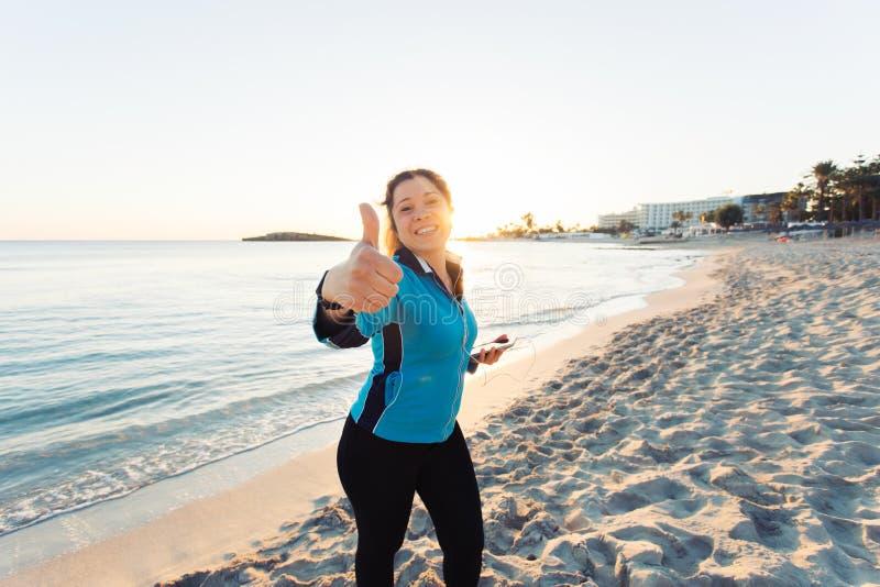 Concepto de deporte, de aptitud, de forma de vida sana y de funcionamiento - la mujer deportiva motivada que hace los pulgares su imágenes de archivo libres de regalías
