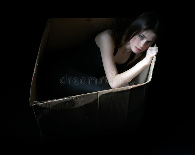 Concepto de desamparados Muchacha trastornada en caja de cartón imagenes de archivo