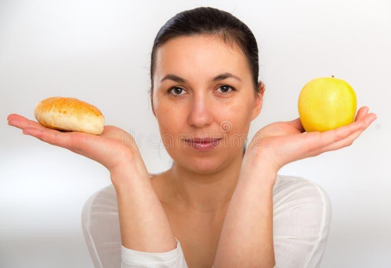 Concepto de dieta Alimento sano Mujer joven hermosa que elige entre las frutas y los dulces foto de archivo