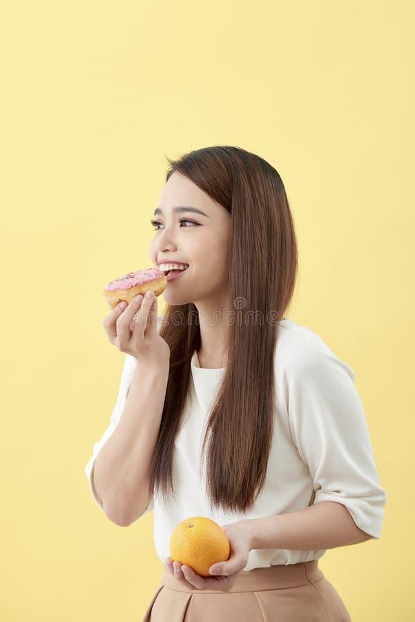 Concepto de dieta Naranja y buñuelo asiáticos jovenes hermosos de la tenencia de la mujer sobre fondo amarillo El elegir entre la foto de archivo libre de regalías