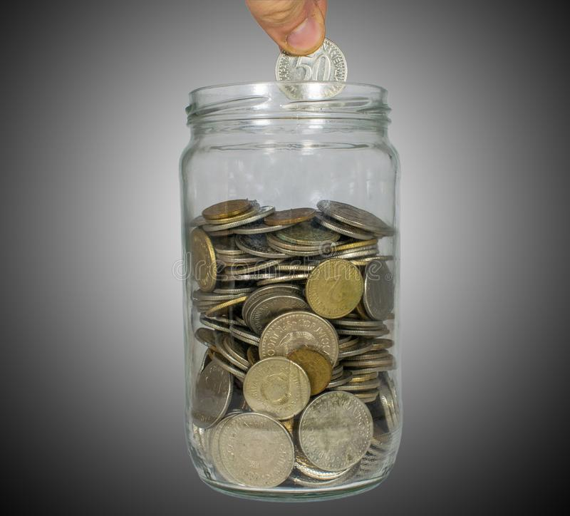 Concepto de dinero del ahorro, poniendo el dinero en el tarro del dinero, ahorros del aumento foto de archivo libre de regalías