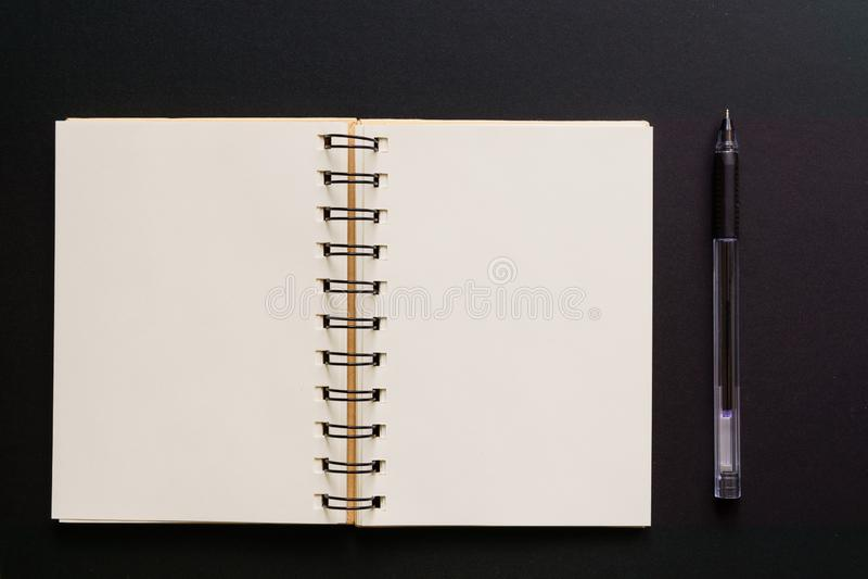 Concepto de diseño - vista superior del bolígrafo vacío del cuaderno y de Kraft en fondo negro Mofa para arriba imagen de archivo libre de regalías