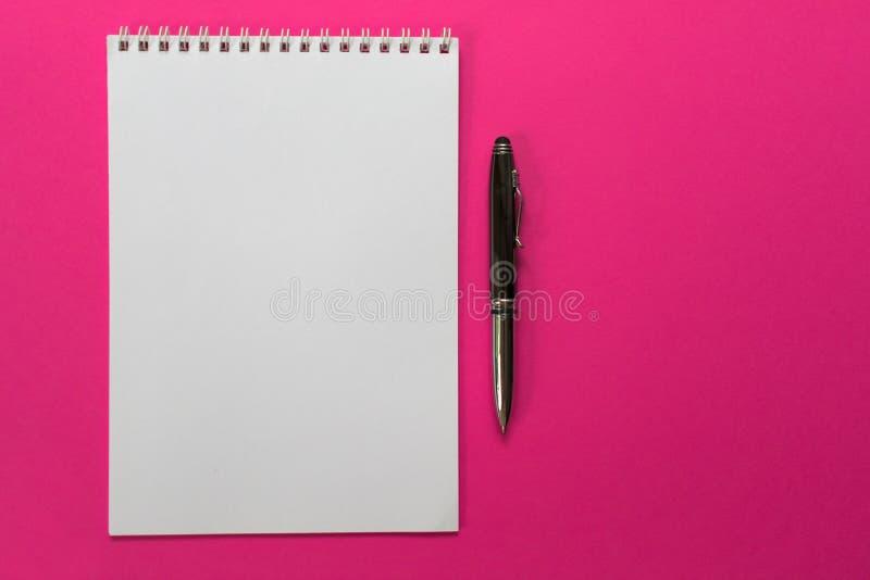 Concepto de dise?o - vista superior de una colecci?n espiral del cuaderno y de las plumas de la escuela en un fondo rosado para l fotos de archivo libres de regalías