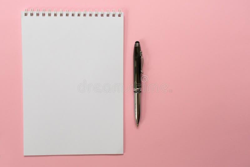 Concepto de dise?o - vista superior de una colecci?n espiral del cuaderno y de las plumas de la escuela en un fondo rosado para l imagen de archivo