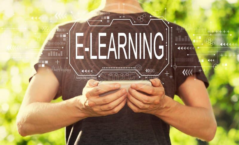 Concepto de e-learning con un hombre sujetando su smartphone imagenes de archivo