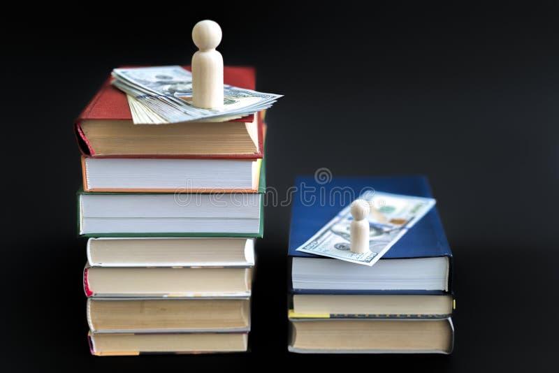 Concepto de educación y de renta Figuras de madera dólares y libros en un fondo negro fotos de archivo