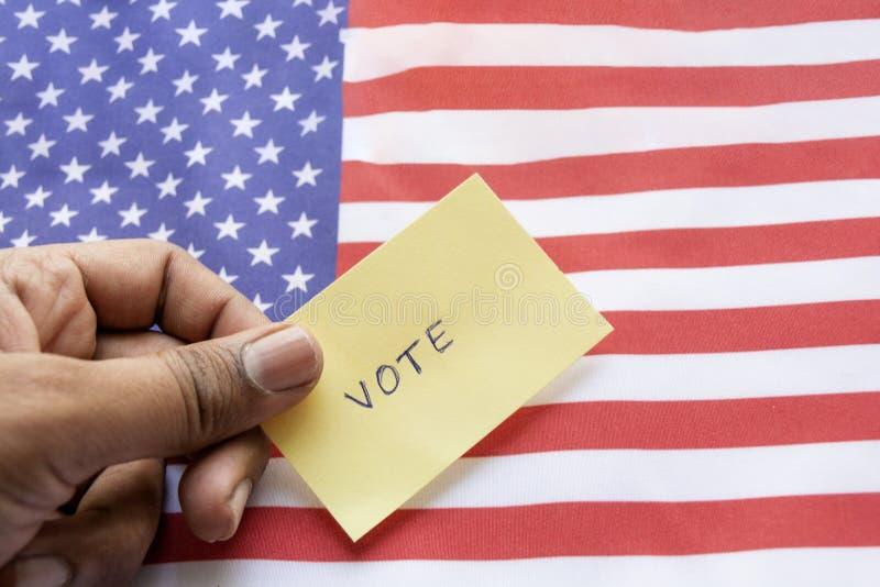 Concepto de elección de los E.E.U.U., etiqueta engomada del voto que se sostiene a disposición en bandera de los E.E.U.U. fotografía de archivo libre de regalías