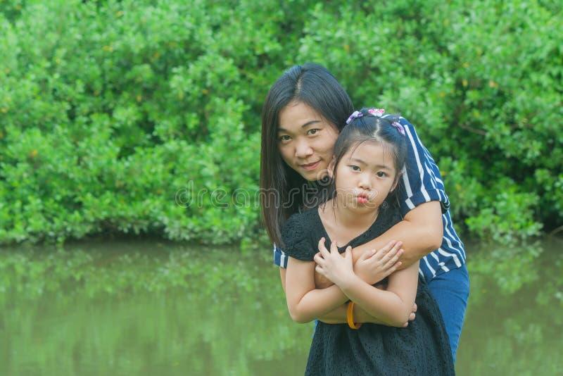 Concepto de familia adorable: Mujer asiática y niños que se colocan en hierba verde, la sonrisa y el abrazo junto imagenes de archivo
