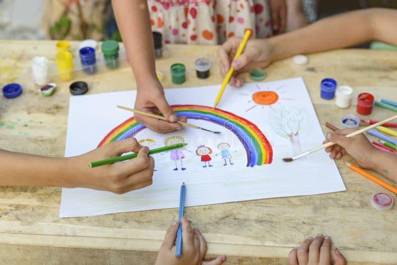 Concepto de familia feliz Co-creación Las manos de los niños dibujan en una hoja de papel: manos del control del padre, de la mad imagen de archivo