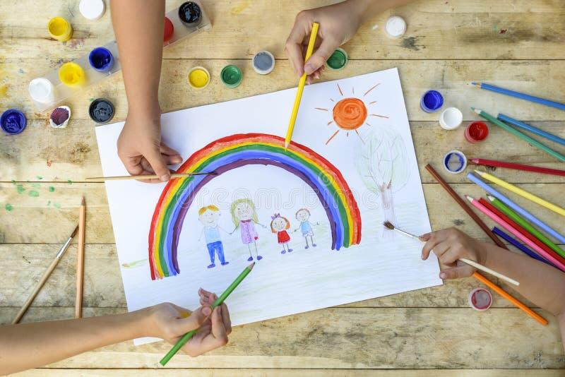 Concepto de familia feliz Co-creación Las manos de los niños dibujan en una hoja de papel: manos del control del padre, de la mad imágenes de archivo libres de regalías