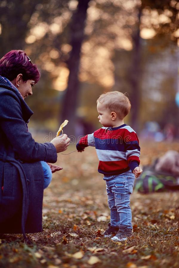 Concepto de familia, infancia, temporada y personas. Madre e hijo en el parque del otoño imagenes de archivo