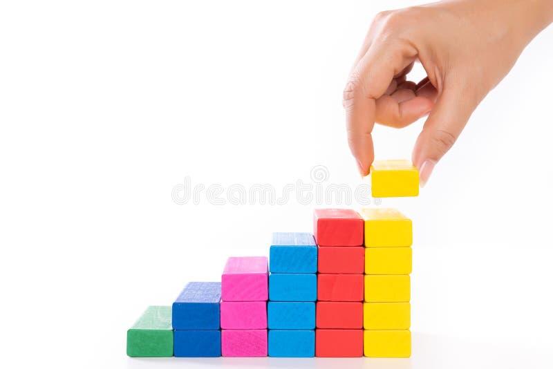 Concepto de fundación del éxito del edificio Las mujeres dan bloques de madera puestos en la forma de una escalera imagenes de archivo