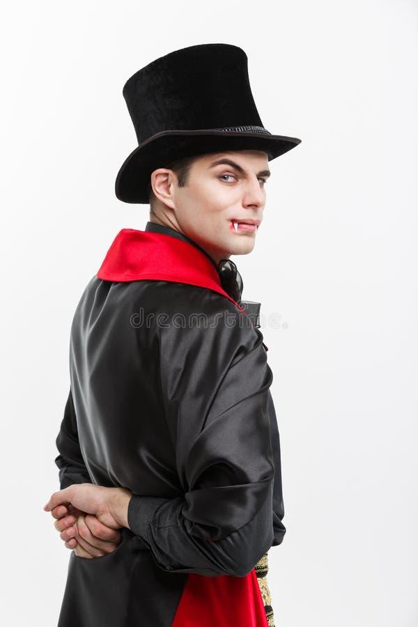 Concepto de Halloween del vampiro - retrato del vampiro caucásico hermoso de la visión trasera en el traje negro y rojo de Hallow fotografía de archivo