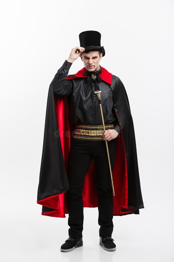Concepto de Halloween del vampiro - retrato integral del vampiro caucásico hermoso en el traje negro y rojo de Halloween imágenes de archivo libres de regalías