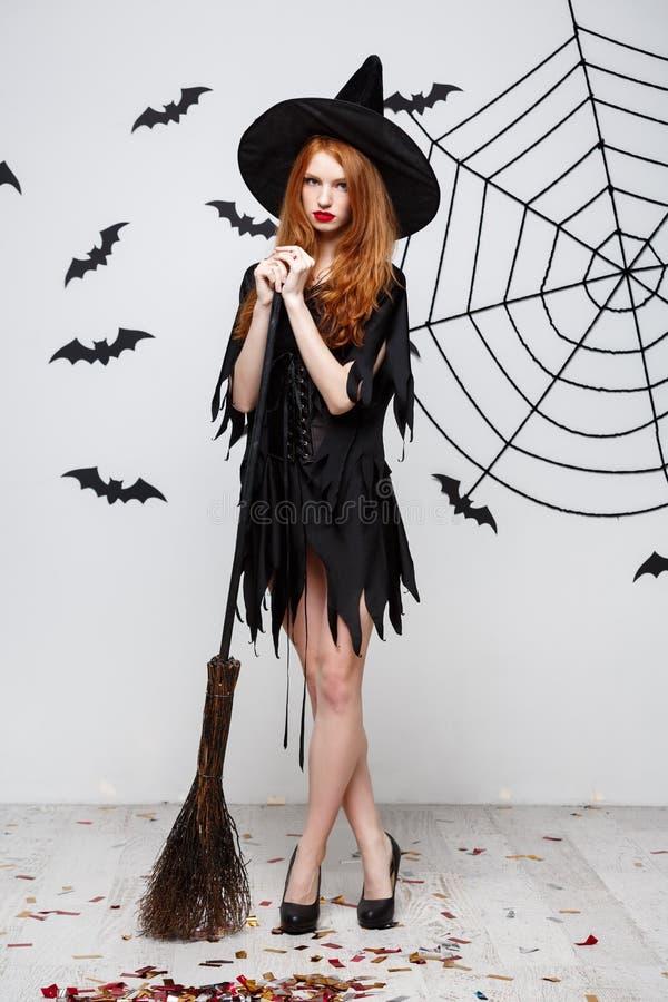 Concepto de Halloween - la bruja elegante feliz goza el jugar con el partido de Halloween del palo de escoba sobre fondo gris fotos de archivo