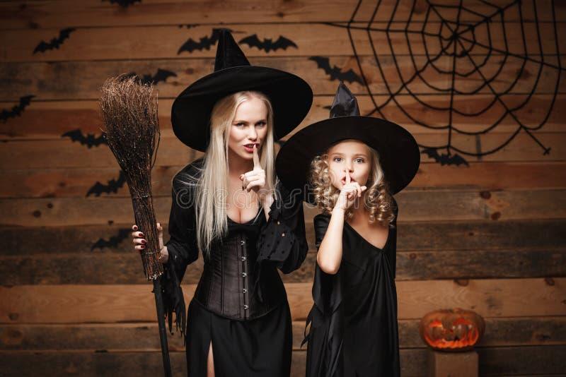 Concepto de Halloween - la madre alegre y su la hija en trajes de la bruja que celebran Halloween que hace silencio gesticulan la fotografía de archivo
