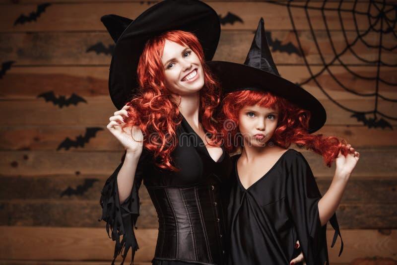 Concepto de Halloween - madre caucásica hermosa y su hija con el pelo rojo largo en trajes de la bruja que celebran la presentaci imagen de archivo libre de regalías