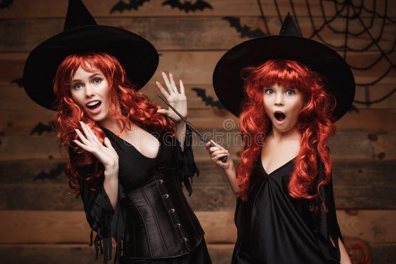 Concepto de Halloween - madre caucásica hermosa y su hija con el pelo rojo largo en trajes de la bruja y vara mágica que celebran fotografía de archivo libre de regalías