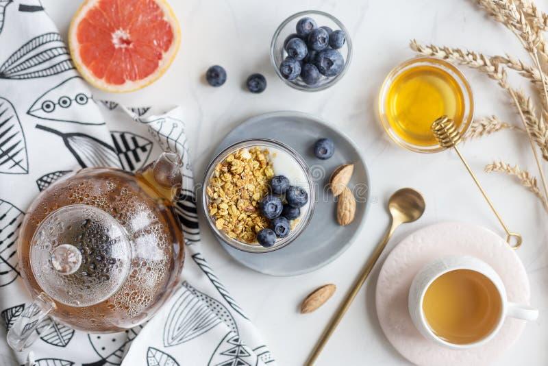 Concepto de harina de avena sana del desayuno con las nueces, bayas y leche, miel, pomelo y té fotos de archivo