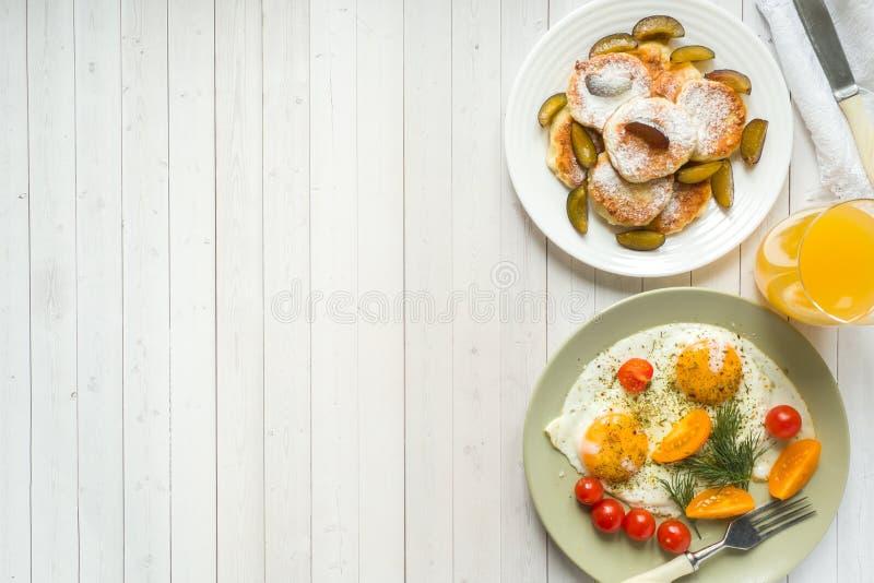 Concepto de huevos fritos del desayuno, de crepes del requesón, de ciruelos y de harina de avena con la leche, zumo de naranja en imágenes de archivo libres de regalías