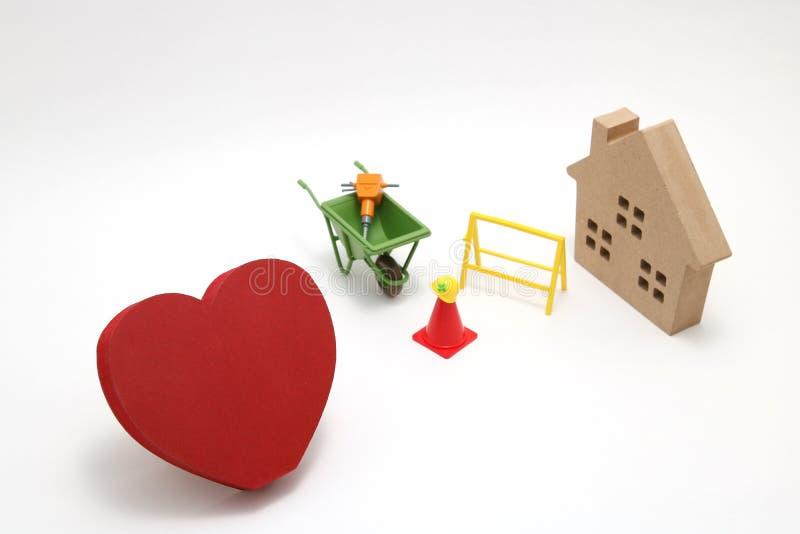 Concepto de imagen de la seguridad Herramientas en forma de corazón rojas de madera, de la casa y de la construcción de la miniat fotografía de archivo