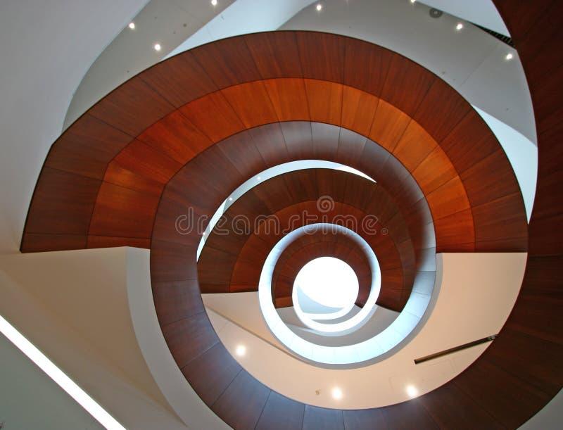 Concepto de infinito El atrio interior de varios pisos con las escaleras espirales suspendidas de madera hincha como el obturador imagen de archivo