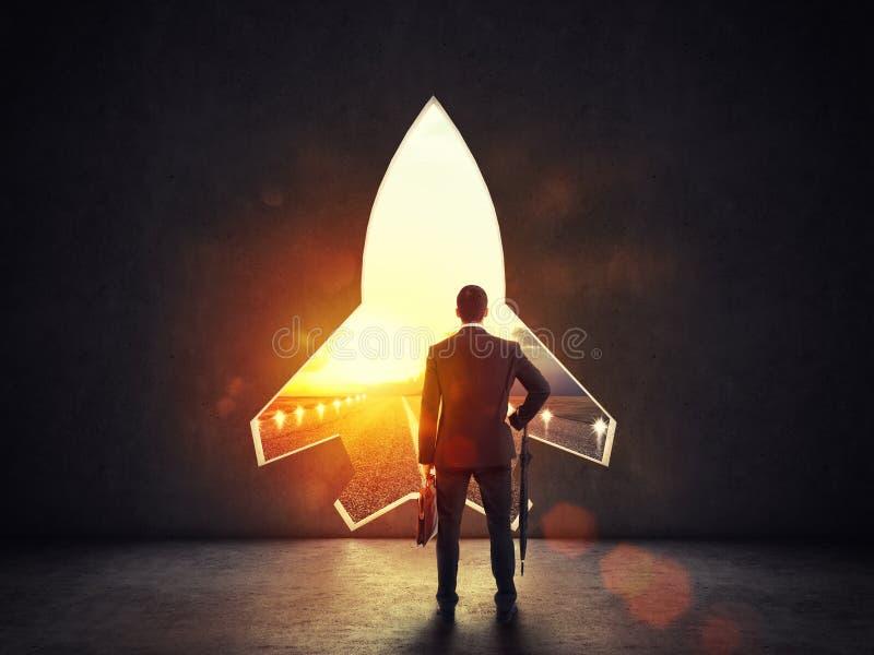 Concepto de inicio con un agujero de la forma del cohete en la pared que refiere a la salida hacia nuevas metas foto de archivo libre de regalías