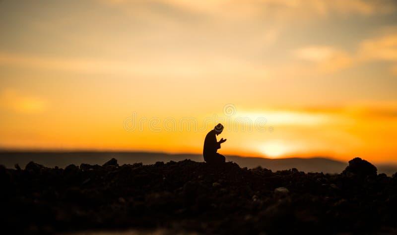 Concepto de Islam de la religi?n. Silueta del hombre que ruega en el fondo de una mezquita en la puesta del sol fotos de archivo libres de regalías