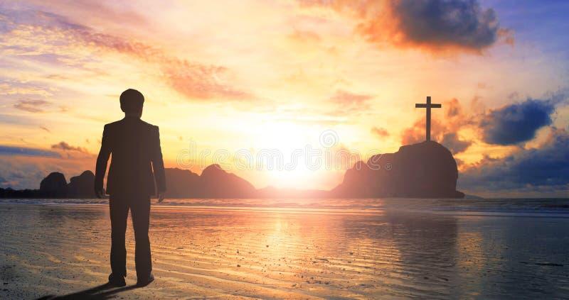 Concepto de la adoración y de la alabanza: hombre de negocios que hace una pausa el mar en la puesta del sol foto de archivo