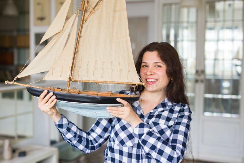 Concepto de la afición, de la recogida, de la nave y de la gente - mujer joven que lleva a cabo la disposición de un velero foto de archivo
