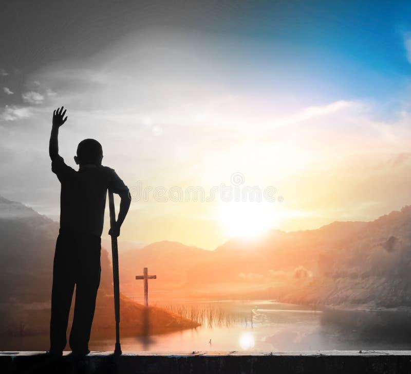 Concepto de la alabanza y de la adoración: Siluetee la situación del ser humano y la cruz en fondo de la puesta del sol del prado imagen de archivo libre de regalías