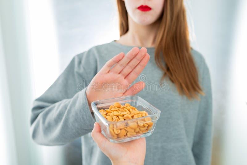 Concepto de la alergia del cacahuete - intolerancia de la comida La chica joven rechaza comer los cacahuetes fotografía de archivo libre de regalías