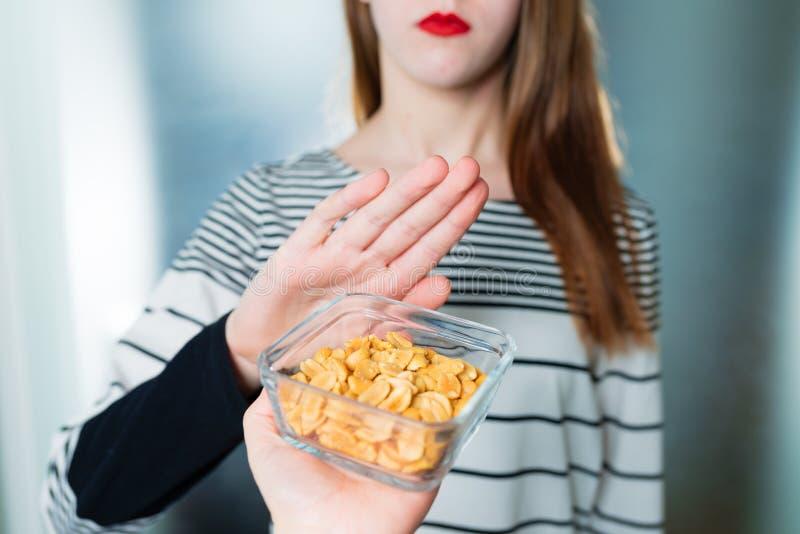 Concepto de la alergia del cacahuete - intolerancia de la comida La chica joven rechaza comer los cacahuetes fotos de archivo