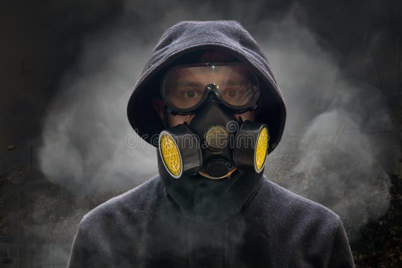 Concepto de la apocalipsis o del armageddon El hombre está llevando la careta antigás Mucho humo alrededor imagen de archivo