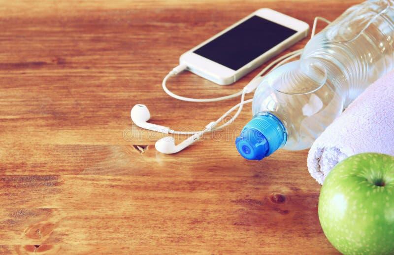 Concepto de la aptitud con la botella del agua, teléfono móvil con los auriculares fotos de archivo libres de regalías