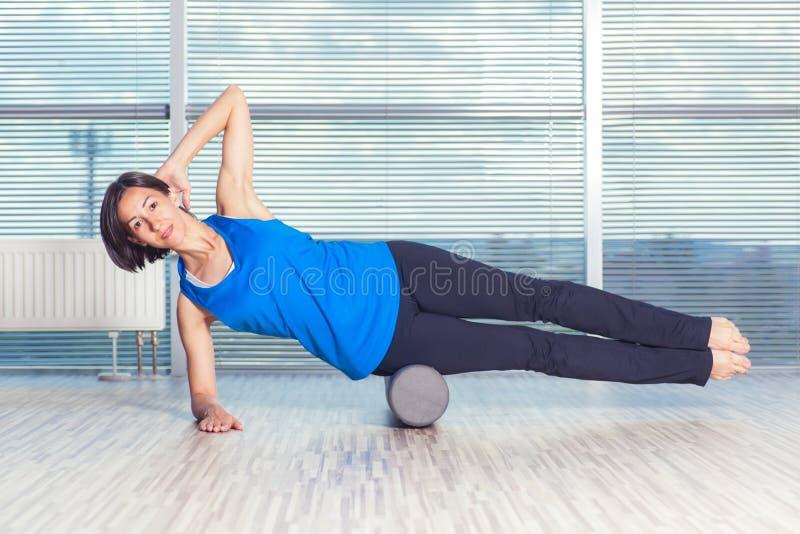 Concepto de la aptitud, del deporte, del entrenamiento y de la forma de vida - mujer que hace pilates en el piso con el rodillo d fotos de archivo