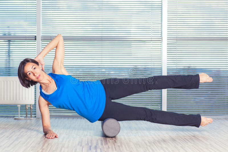 Concepto de la aptitud, del deporte, del entrenamiento y de la forma de vida - mujer que hace pilates en el piso con el rodillo d fotografía de archivo
