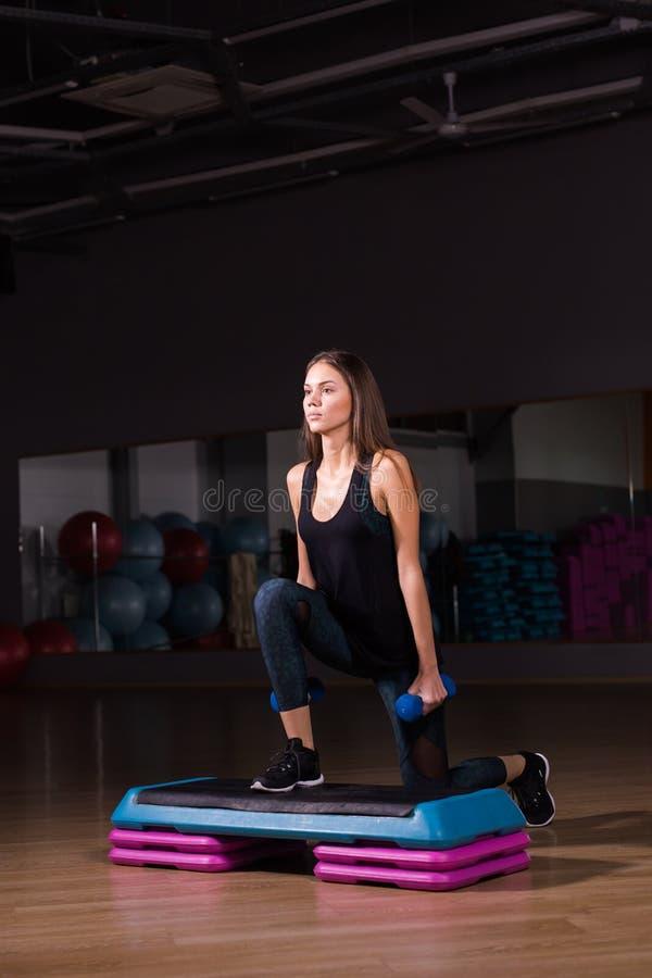 Concepto de la aptitud, del deporte, del entrenamiento y de la forma de vida - mujer con pesas de gimnasia en gimnasio foto de archivo libre de regalías