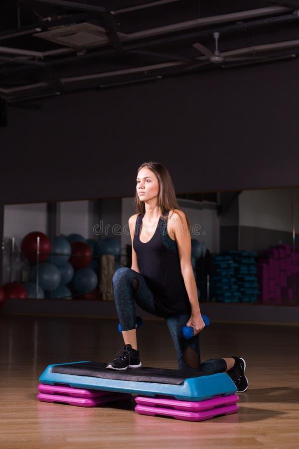 Concepto de la aptitud, del deporte, del entrenamiento y de la forma de vida - mujer con pesas de gimnasia en gimnasio imagenes de archivo