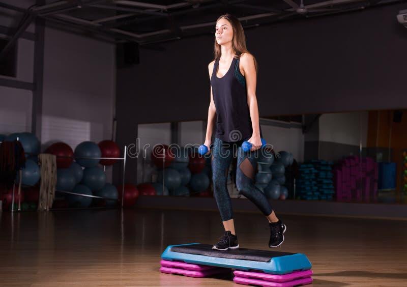 Concepto de la aptitud, del deporte, del entrenamiento y de la forma de vida - mujer con pesas de gimnasia en gimnasio imagen de archivo libre de regalías