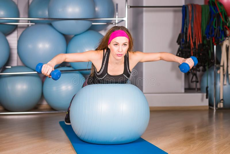 Concepto de la aptitud, del deporte, del entrenamiento y de la forma de vida - mujer sonriente con pesas de gimnasia y bola del e fotografía de archivo libre de regalías