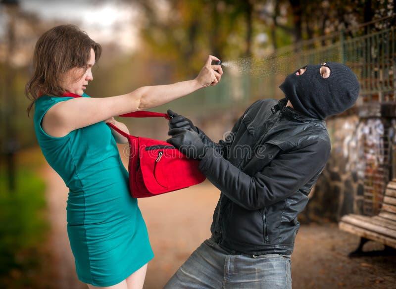 Concepto de la autodefensa Al hombre en pasamontañas atacó a la mujer joven está utilizando el spray de pimienta fotos de archivo