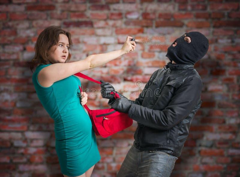 Concepto de la autodefensa La mujer joven está luchando con el ladrón y está utilizando el spray de pimienta fotos de archivo libres de regalías