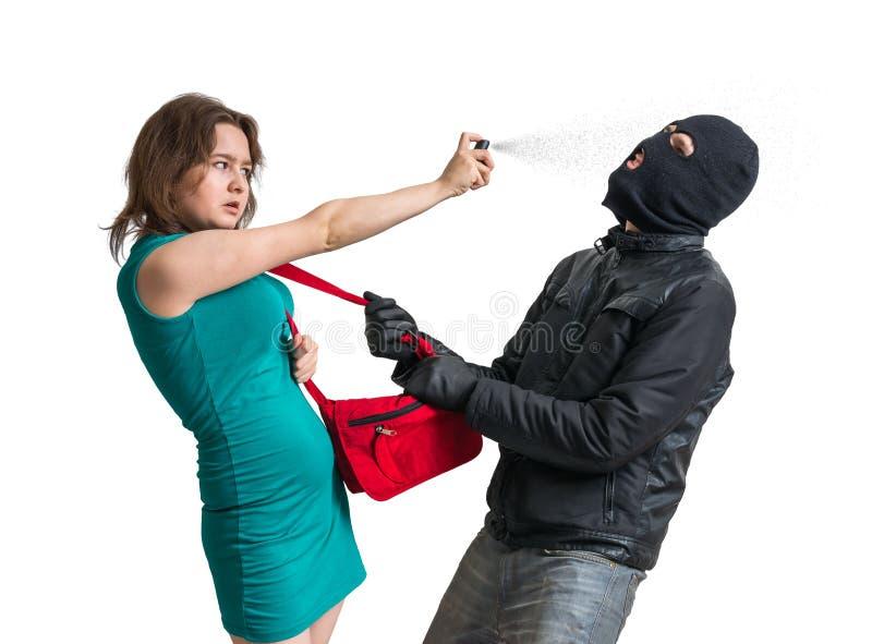 Concepto de la autodefensa La mujer joven está luchando con el ladrón y está utilizando el spray de pimienta imágenes de archivo libres de regalías
