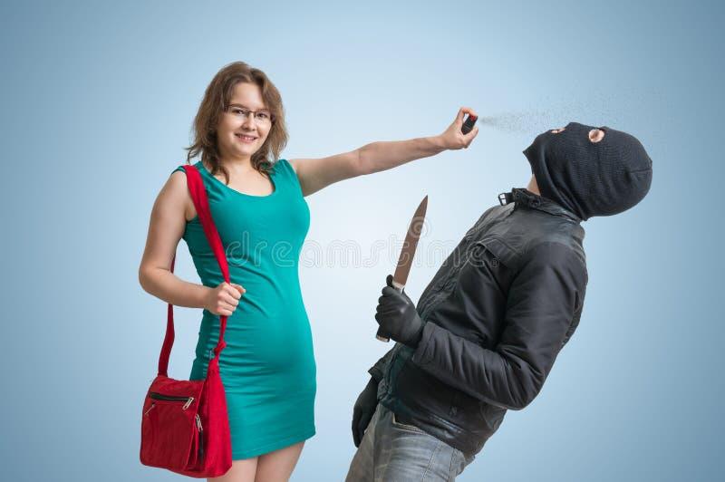 Concepto de la autodefensa La mujer joven se está defendiendo con el spray de pimienta fotografía de archivo libre de regalías