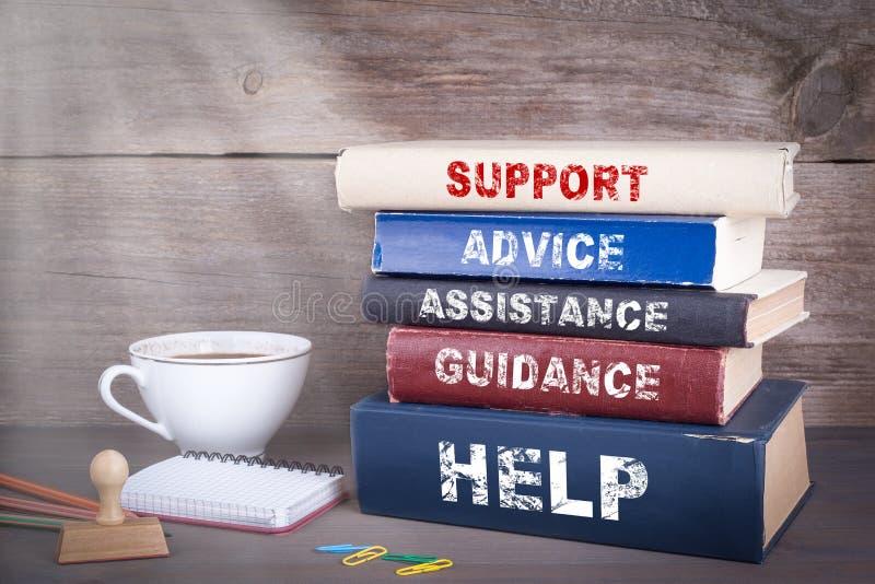 Concepto de la ayuda Pila de libros en el escritorio de madera imagen de archivo