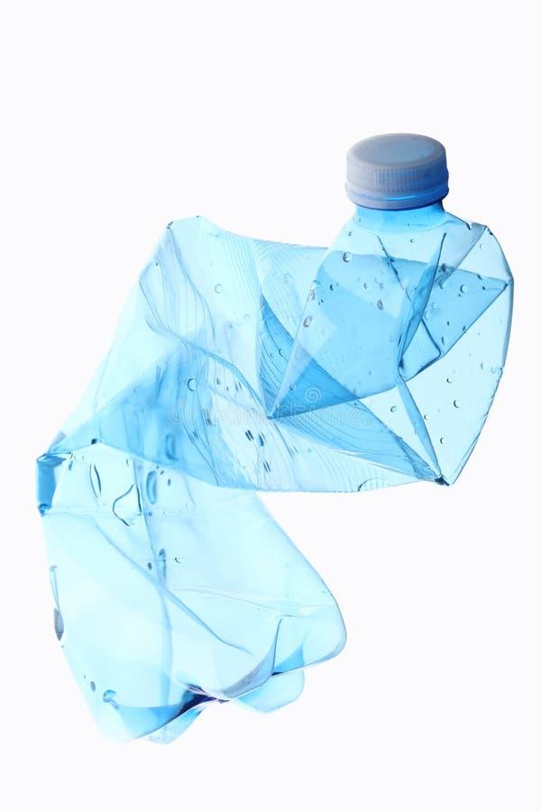 Concepto de la basura: botella plástica machacada vacía aislada en el fondo blanco con la trayectoria de recortes y el espacio de fotografía de archivo