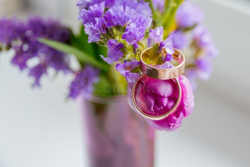 Concepto de la boda: ramo de rosa, de tulipanes púrpuras y de dos anillos de oro Rama de florecimiento con las flores púrpuras, v fotografía de archivo libre de regalías