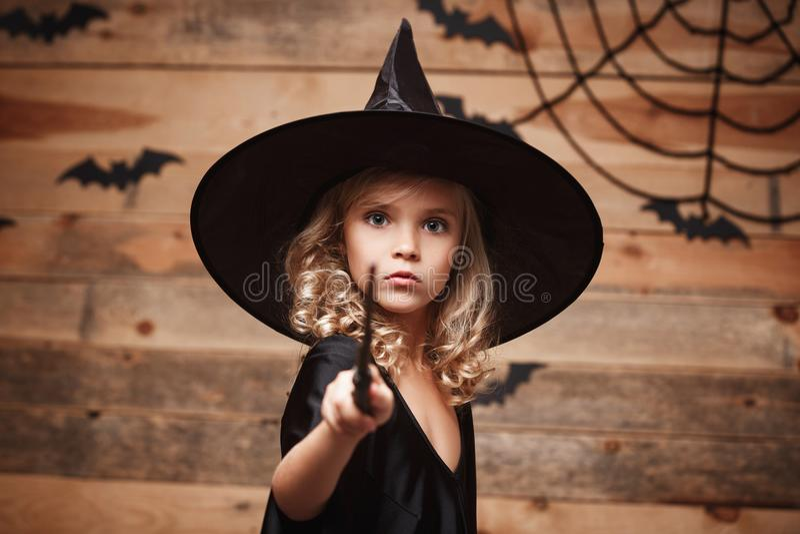Concepto de la bruja de Halloween - el pequeño niño de la bruja goza el jugar con la vara mágica sobre fondo del web del palo y d imagen de archivo